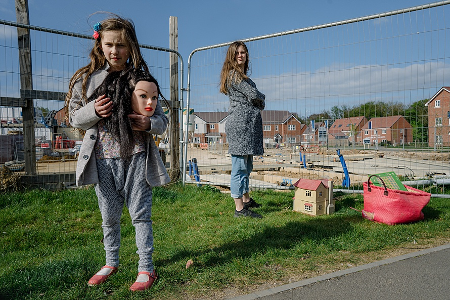 Girls on roadside by deserted building site